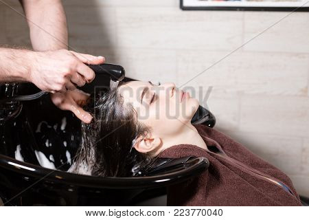 beautiful girl washes her hair before a haircut in a beauty salon. hair washing at a hairdressing, young caucasian girl. professional shampoo. stylist hairdresser man.