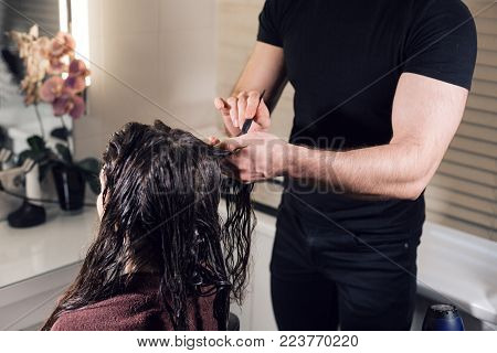 Closeup hairdresser man makes hairstyle for young woman in beauty salon.