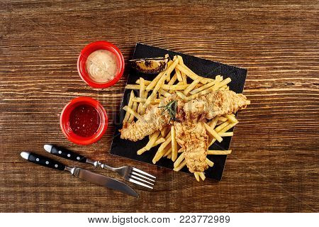 Black plate with fish and chips, mayo and ketchup on wooden background. Still life. Copy space