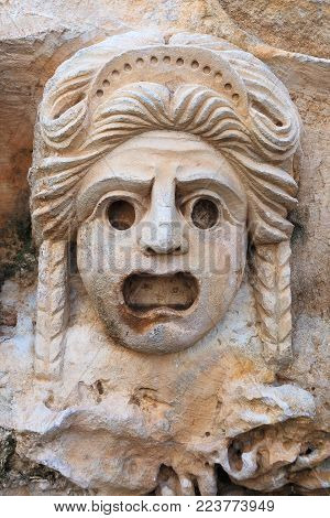 Women's stone theatrical mask carved in stone. Close up. Ancient Lycia, Turkey.