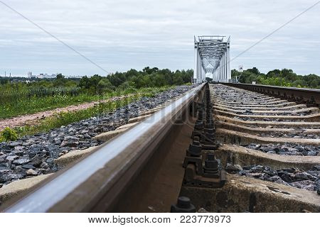 Fastening the rail to the sleepers on the rail track and railway bridge in the background