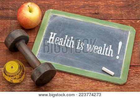 health is wealth concept -  slate blackboard sign against weathered red painted barn wood with a dumbbell, apple and tape measure