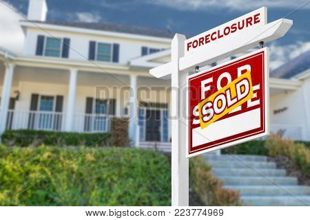 Right Facing Foreclosure Sold For Sale Real Estate Sign in Front of House.