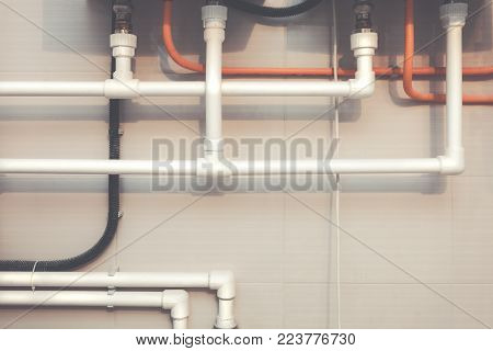 White plastic water pipes of plumbing system with Y-branch fitting, black corrugated tube and wall with ceramic tiles. Picture with tone effect
