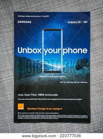 PARIS, FRANCE - APR 26, 2017: Unbox Your phone advertising campaign for Samsung Galaxy Smartphone S8 from Orange Telecom on the last page of a fashion magazine newspaper