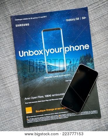 PARIS, FRANCE - APR 26, 2017: Unbox Your phone advertising campaign for Samsung Galaxy Smartphone S8 from Orange Telecom with Apple iPhone smartphone SE on cover