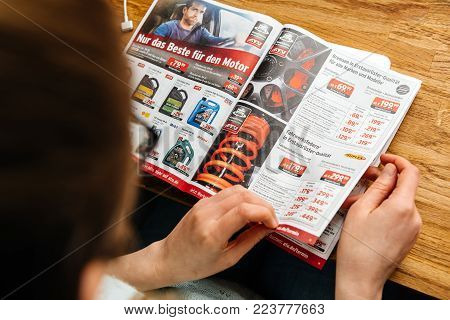 PARIS, FRANCE - APR 26, 2017: Elevated view woman reading A.T.U Auto-Teile-Unger German automotive services advertising leaflet with accessories and car care products such as car oil and lubricants