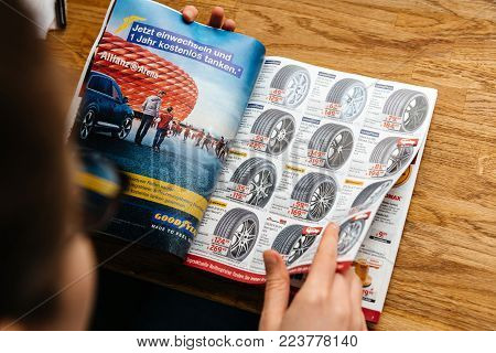PARIS, FRANCE - APR 26, 2017: Elevated view woman reading A.T.U Auto-Teile-Unger German automotive services advertising leaflet with accessories such as aluminum rims tires winter tires and chains