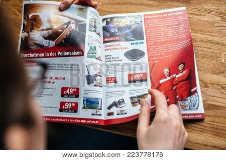 PARIS, FRANCE - APR 26, 2017: Elevated view woman reading A.T.U Auto-Teile-Unger German automotive services advertising leaflet with accessories and car care products