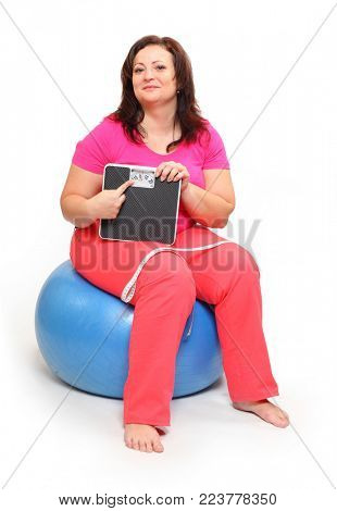 Overweight woman with measure tape and weighing machine. Healthy lifestyle theme. Obesity and other civilization illness.