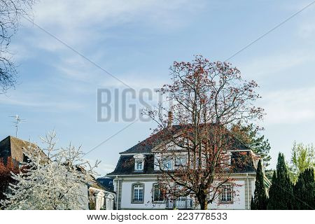 Big Luxury French real estate property house building on a warm day with summer blue sky and scattered clouds