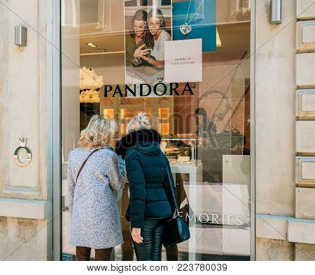 PARIS, FRANCE - APR 21, 2017: Two seniors woman buying jewelry from Pandora boutique jewelry store deciding for the best gift during sale holiday season
