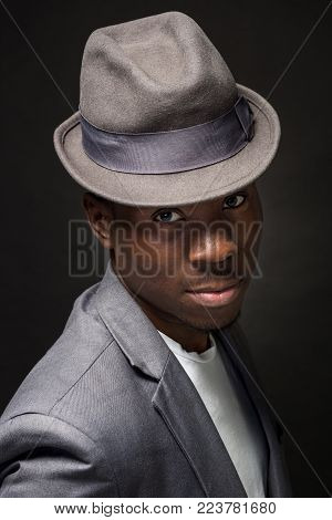 Close-up portrait of handsome black man with charming smile. Studio shot of well-dressed african guy wears hat and jacket, on dark background