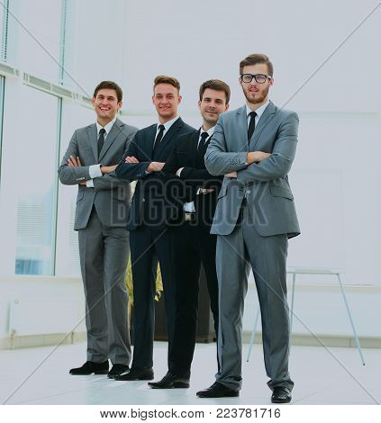 Business team in a line smiling at the camera.