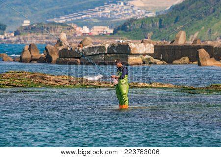 KEELUNG, TAIWAN - APRIL 04: Fisherman catching fish in the ocean near Badouzi coastal park on April 04, 2017 in Keelung