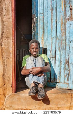 African child sitting in front if the door in the village, Botswana