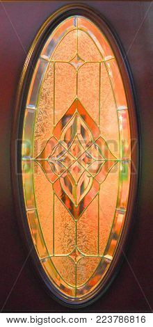 Antique oval Art Deco style stain glass window, geometric design. Vintage stain glass window set in a dark wood door. Geometric design and shades of orange, brown and green lit up by sunlight .