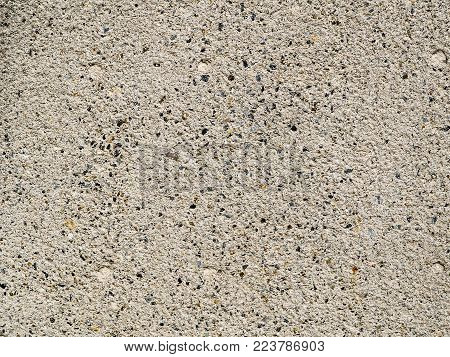 Weathered concrete cement wall background, rough texture. Concrete exterior wall with authentic texture,  weathered with small speckled stones and pebbles.