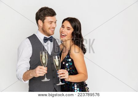 celebration and holidays concept - happy couple with glasses drinking non alcoholic champagne at party