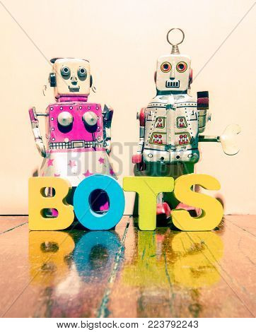 two retro robot toys and the word BOTS on a wooden floor