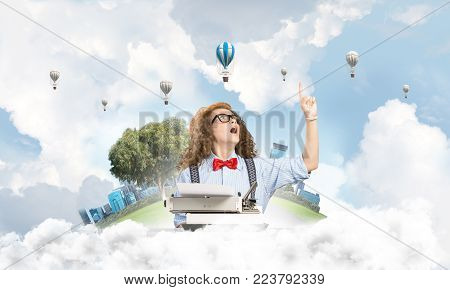 Beautiful woman writer in hat and eyeglasses using typing machine and pointing upside while sitting at the table with floating city island and cloudy skyscape with flying aerostats on background.
