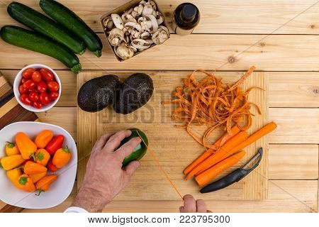 Chef slicing fresh vegetables for cooking on a wooden chopping board holding a green pepper with peeled carrots, zucchini, mushrooms, tomatoes,ripe avocado pears and carrots in an overhead view