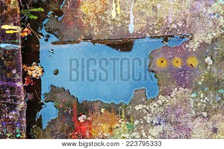 Reflection of the sky in a water puddle on an old spattered with paint concrete. Close up.
