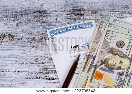 Filing federal taxes for a refund - tax form currency and r on wooden bench