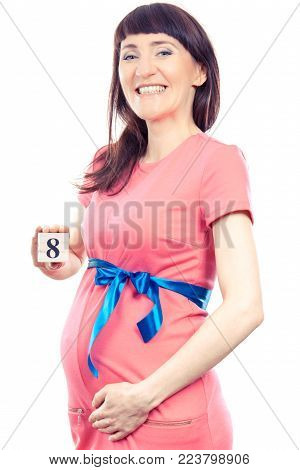 Smiling pregnant woman in pink dress with blue ribbon showing number of eighth month of pregnancy, concept of extending family and expecting for newborn