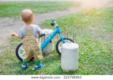 Cute little Asian 1 year old toddler baby boy child in dungarees costume and wearing baby shoe parked the bicycle in the summer park outdoor on nature, kids sports concept