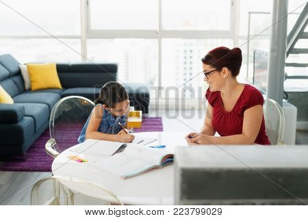 Hispanic mother and female child, with mom helping daughter with school homework.