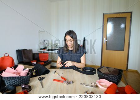 female fixing snap on leather pattern using special mechanism. Young designer decided to try to make women bags for sale. Black-haired girl with red nails wearing grey T-shirt sitting near table in workshop. Concept of creative work, own business or handw