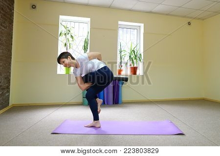 Beautiful dark-haired woman sits on floor on yoga mat and performs stretching exercises. Girl dressed in sporty black tights and white T-shirt, short hair trimmed. Inside spacious and bright, in room large windows, on windowsills pots with flowers. Concep
