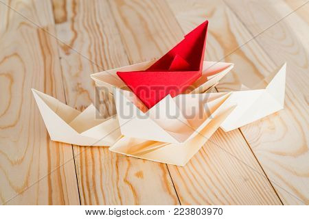 leadership concept. origami paper boat leading white ships crossing red finish line. Rivalry, business, success and efficiency concept