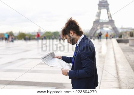 Handsome smiling journalist reading French public press close to Eiffel Tower. Attractive young man dressed in black suit, white shirt with blue tie. Cute guy has long fleecy hair and dark beard.  Concept of informing people with press  Mass Media.
