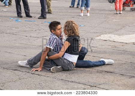 Constitution Square, Mexico City - November 02, 2009. An anonymous couple of young lovers sitting on the floor of the Constitution Square in Mexico City.