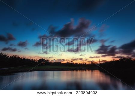 Beautiful sunset over the lake near the golf course in a tropical resort in Punta Cana, Dominican Republic