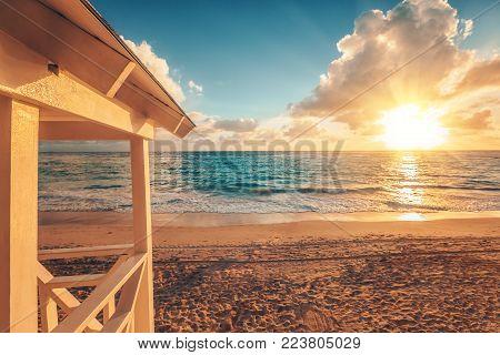 Punta Cana sunrise over Caribbean beach with lifeguard station.