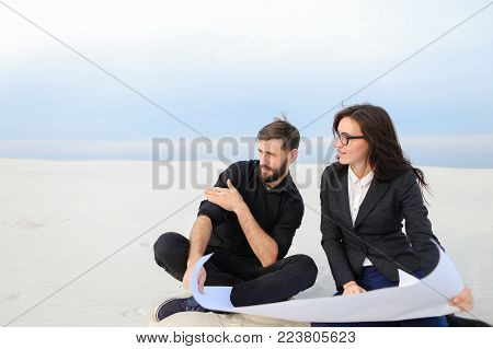 translators wife and husband move to alien city, married couple planning house at seaside. Young bearded fellow and fair-haired girl in glasses sitting on sand with whatman paper.