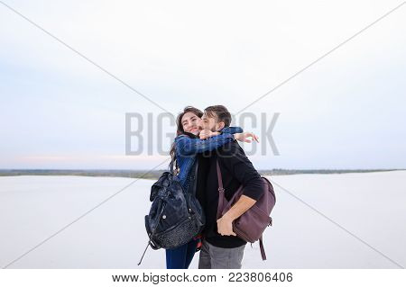 Husband tell wife about purchase plot of land for house at seaside, happy lady jumping for joy embrace bearded guy. Fellow wearing black hoody kiss girl in jean jacket black scarf. Concept of property for sale, beautiful landscapes or fashionable clothes.