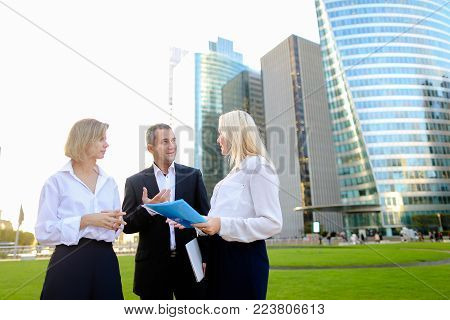 Beautiful businesswomen keeping blue document case talking with cheerful male boss outside. Concept of speaking with partners and joking about work. Pretty ladies dressed in white shirts smiling with man.