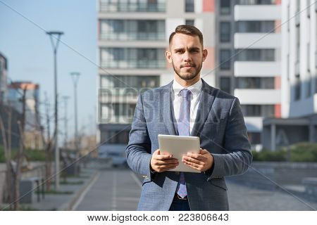 Businessman or real estate agent ready to discuss business and stands with tablet computer against new building