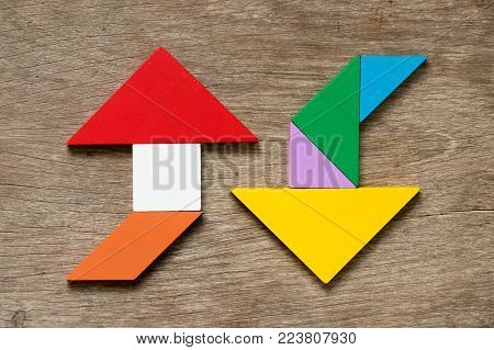 Colorful tangram puzzle in upward and downward arrow shape on wood background