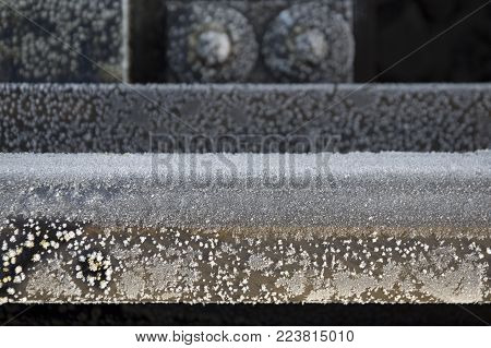 Beautiful frozen metal rail fragment in winter close-up