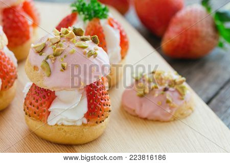Strawberry choux cream in close up view. Combination with choux pastry whipped cream strawberries glaze with white chocolate and chopped pistachios. Sweet and delicious dessert for Valentine. Homemade bakery. Cream puff or choux cream ready to served.