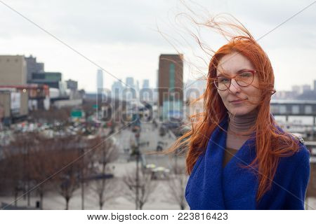 Young cute red-haired woman in a blue coat and glasses standing on the background of the big city, her hair fluttering in the wind, portrait
