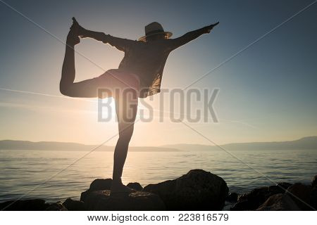 Yoga woman on beach. Active summer vacation. Beach Yoga. Yoga pose at sunset.