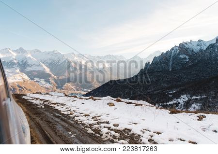 A view from the SUV's driver's door to a countryside rural road with dirt and a valley of mountains in the distance. The concept of traveling on off-road cars in the mountains in spring and autumn. Beautiful mountains sunset