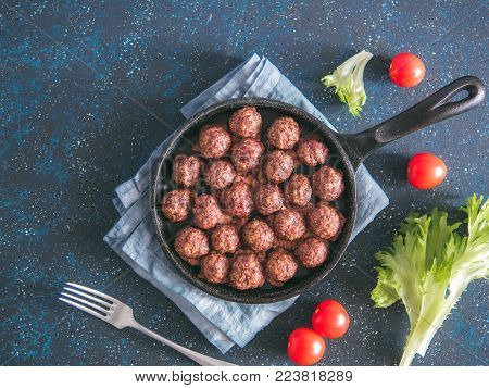 Homemade roasted beef meatballs in cast-iron skillet on dark blue background. Top view or flat-lay. Copy space for text.