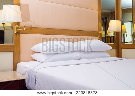 Hotel bed, quilt bed white pillows on white bed in bedroom, Bedroom classic design with furnishing, King sized bed in a luxury hotel room with copy space